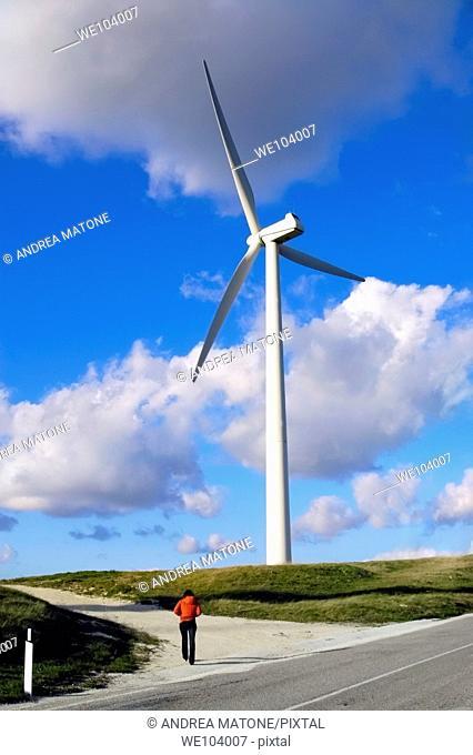 A woman walking towards a wind turbine