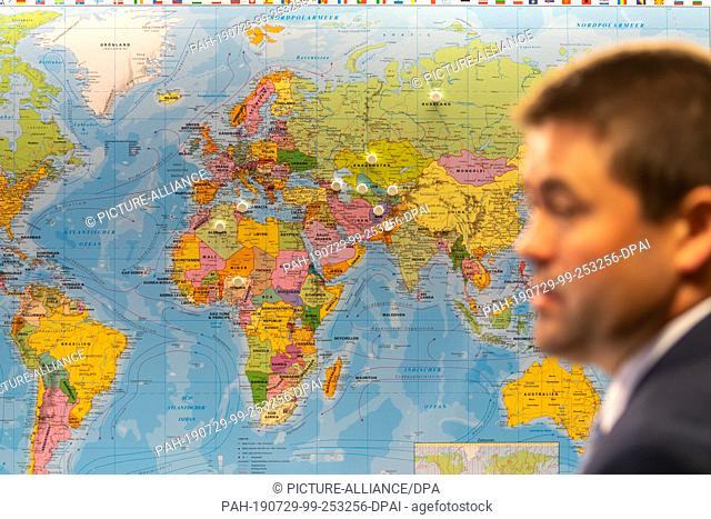 29 July 2019, Bavaria, Manching: A man is standing in front of a world map with various markings before the start of the press conference on the annual balance...