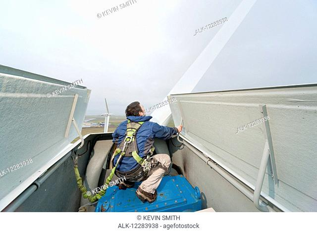 Alaska native technican checking for blade damage atop a wind turbine, St. Paul Island, Southwestern Alaska, USA, Summer