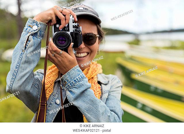 Finland, Lapland, portrait of smiling young woman taking picture with a camera at the lakeside