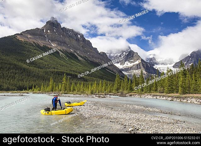 Paddler prepares to launch yellow inflatable raft into scenic river