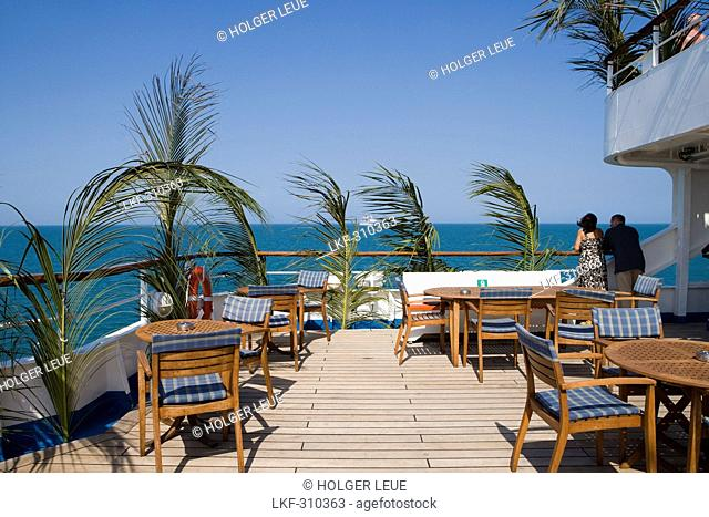 Palm fronds on railing and deck chairs and tables aboard Cruiseship MS Delphin Hansa Kreuzfahrten, Caribbean Sea