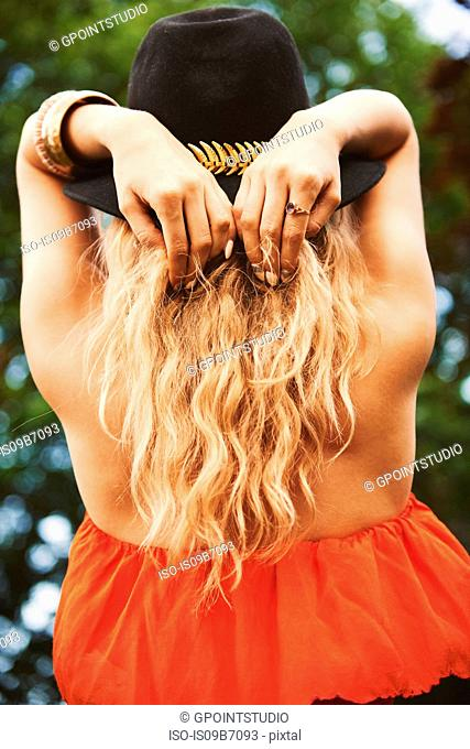 Rear view of young boho woman in trilby with hands behind head at festival