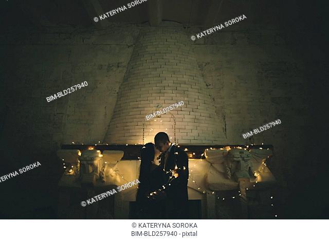 String lights on Caucasian couple near fireplace