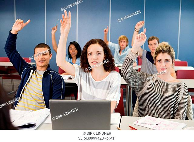 University students holding up hands in class