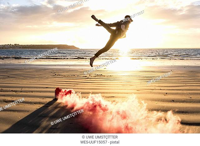 Man doing movement training at the beach with colorful smoke at sunset