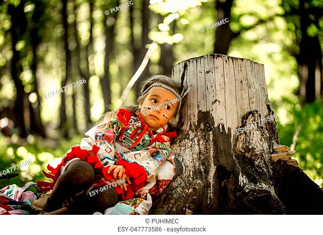 beautiful little girl playing outdoors in Indians ,eating an Apple sitting on a stump