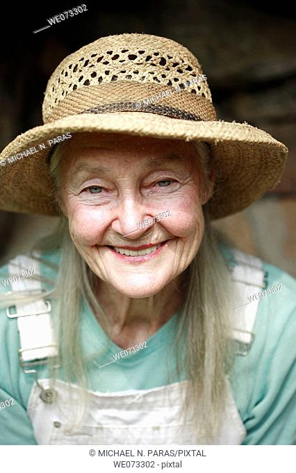 Senior woman with straw hat looking into camera