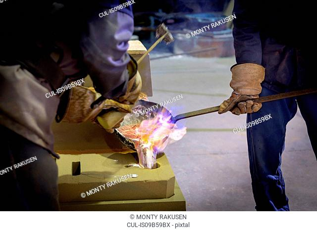 Workers pouring aluminium alloy sample in precision casting factory