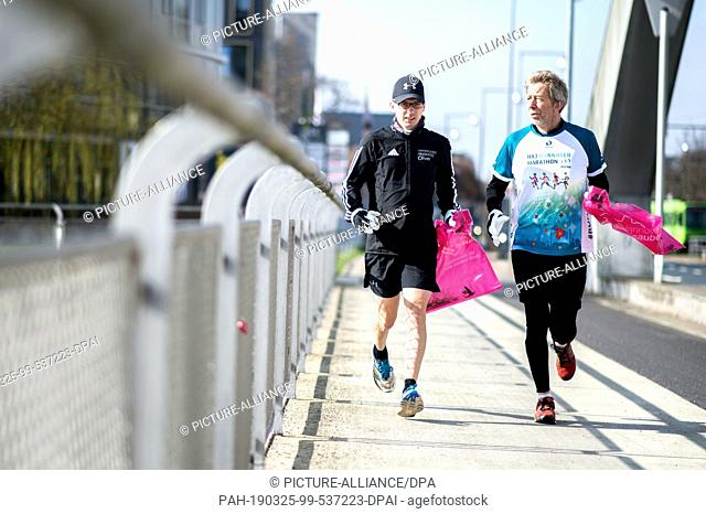 24 March 2019, Lower Saxony, Hannover: Jogger Oliver and Michael Kramer, press spokesman for the Hannover Marathon, walk over the Noltemeyer Bridge in the...