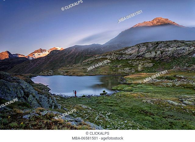 Photographer in action on the shore of the alpine lake at dawn Minor Valley High Valtellina Livigno Lombardy Italy Europe