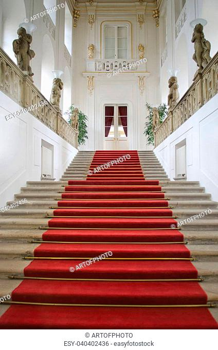 Elegant staircase with red carpet in luxurious palace or mansion