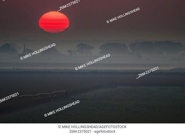 A temperature inversion creates a sun mirage over a foggy eastern Nebraska landscape