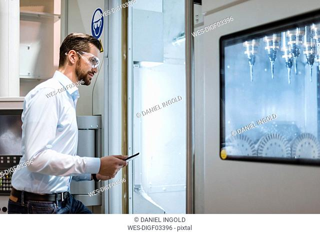 Businessman with tablet wearing safety goggles examining machine in factory looking