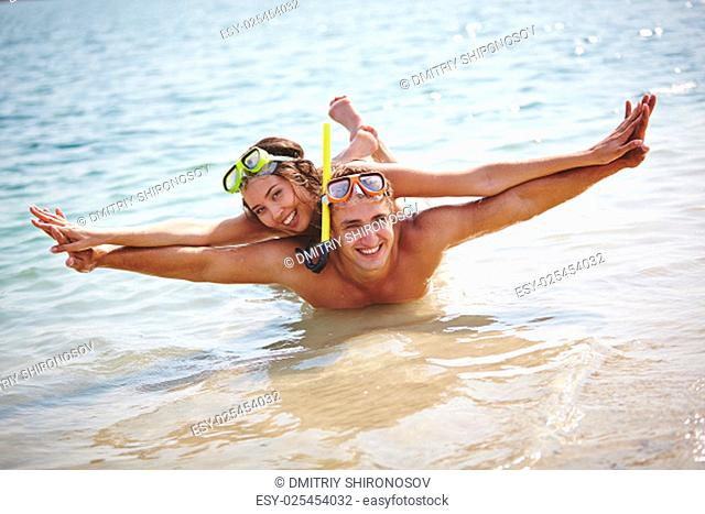 Happy couple in scuba diving equipment looking at camera in water