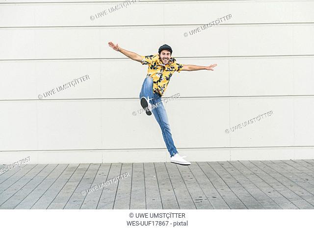 Young man wearing flat hat and aloha shirt, jumping for joy