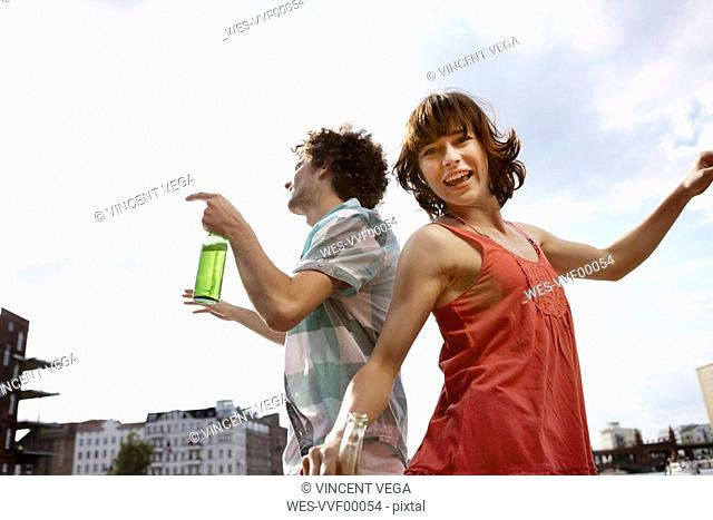 Germany, Berlin, Young couple dancing, laughing, portrait