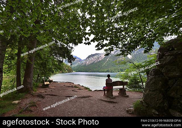12 June 2021, Bavaria, Schwangau: A hiker sits on a bench on the shore of the Alpsee. Photo: Karl-Josef Hildenbrand/dpa. - Schwangau/Bavaria/Germany