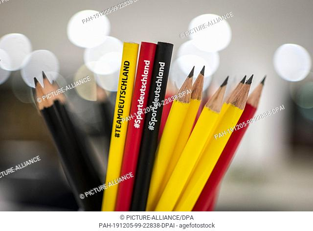 """ILLUSTRATION - 05 December 2019, Hessen, Frankfurt/Main: Pencils in the colours black-red-gold and the inscriptions """"""""#Sportdeutschland"""""""" and..."""
