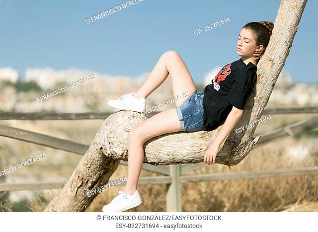 Teenage girl asleep on top of a tree. Take place in Muxamel, province of Alicante, Spain
