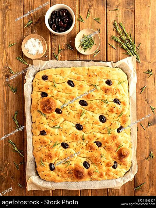 Traditional Italian whole focaccia bread with olives and rosemary