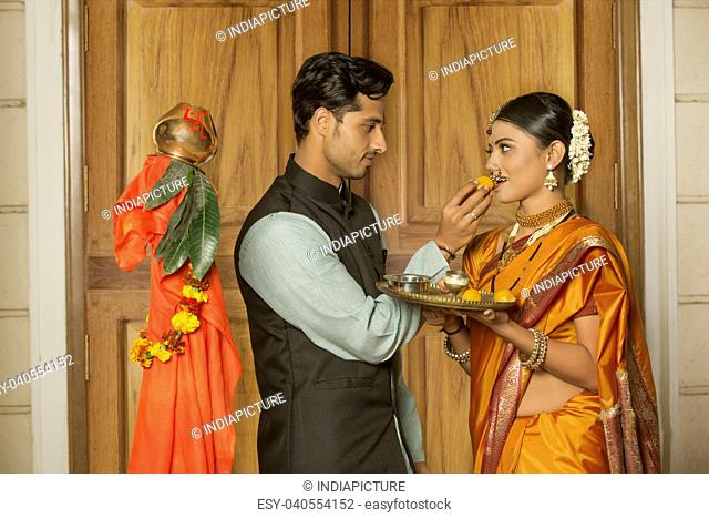 Maharashtrian man in traditional dress offering sweet to her wife while celebrating gudi padwa festival