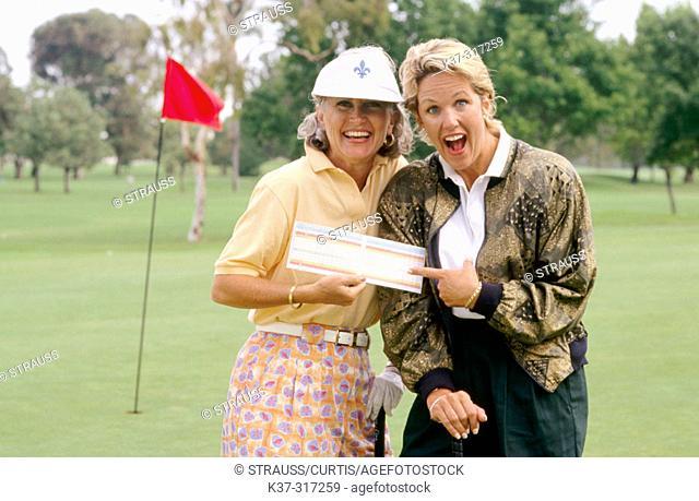 Golfing women showing their score cards