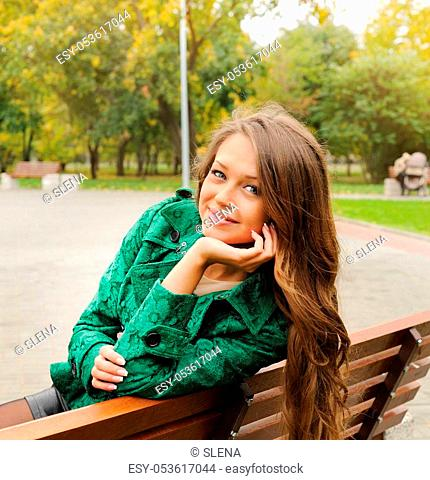 Beautiful yound woman portrait dressed in emerald green coat sitting in autumn park