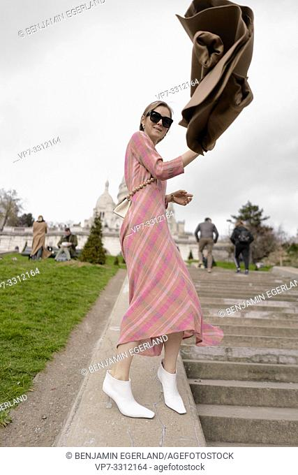 fashionable blogger woman on stairs in front of touristic sight Basilica Sacré-Cœur, during fashion week, in city Paris, France, in city Paris, France