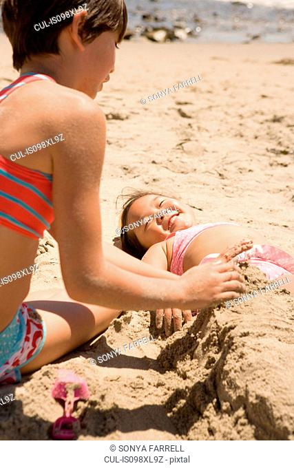 Girl burying other girl in sand on beach