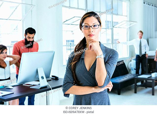 Businesswoman, colleagues working on computer by office window