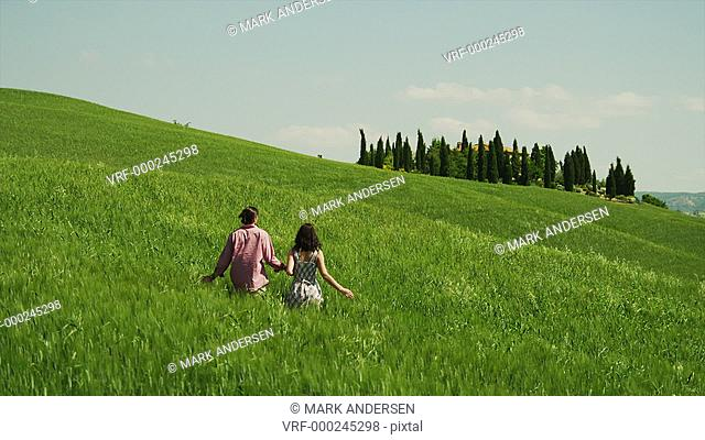 WS Couple walking and kissing on meadow / Tuscany, Italy