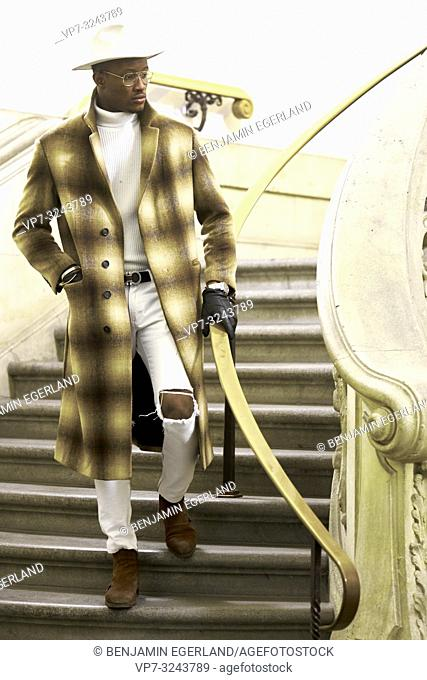 stylish wealthy man wearing expensive clothes, standing on stairs, in city Munich, Germany