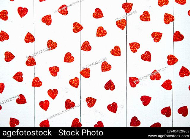 Valentine's Day decoration composition. Heart shaped red sequins placed on white wooden table. Romantic background. Flat lay, top view