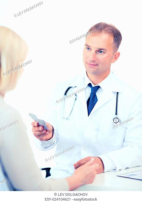 healthcare and medical concept - doctor giving tablets to patient in hospital