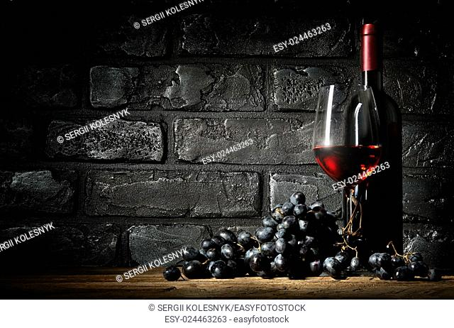 Bunch of grapes and wine on a black brick background