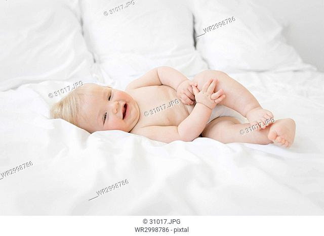Baby boy with blond hair lying on a bed with white duvet