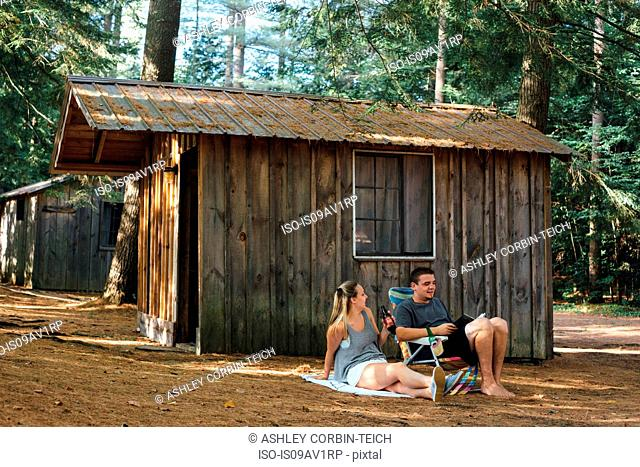 Young couple relaxing outside hut in forest