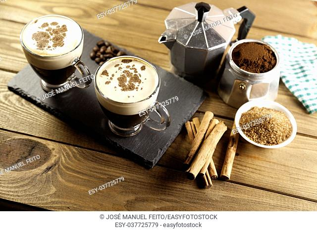two cup of coffee, Italian coffee maker, coffee beans, cinnamon, napkin and brown sugar bowl on wood table