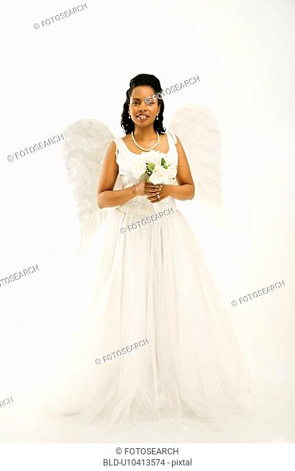Angelic mid-adult African-American bride holding a bouquet on white background