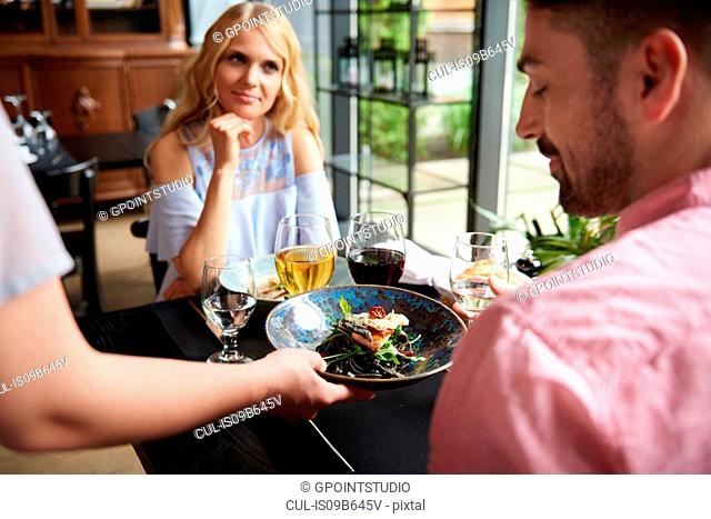 Over shoulder view of waitress serving lunch to couple at restaurant table