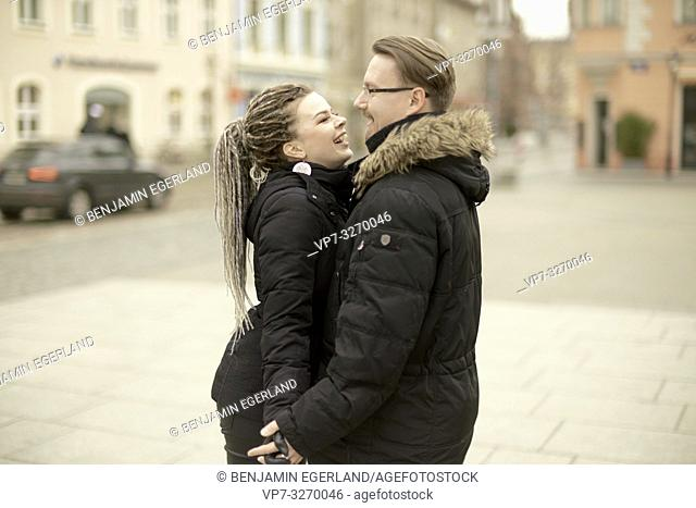 happy couple in town, looking at each other, side view, in Cottbus, Brandenburg, Germany