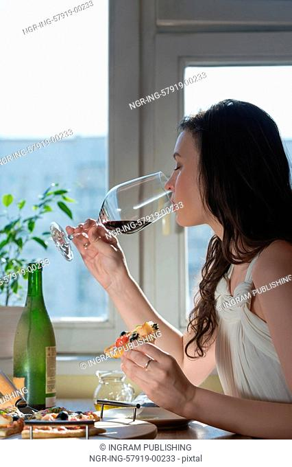 Beautiful young woman eating homemade pizza and drinking red wine at home