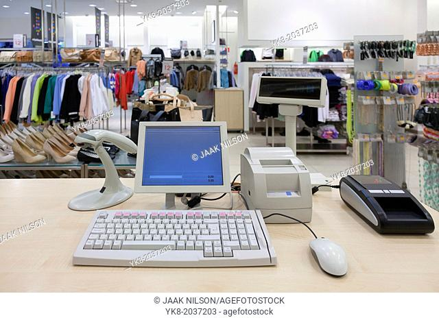 Fashion clothing store. Cashier register, scanner, computer on sales counter in shop