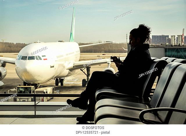 Passenger sitting in airport terminal using her smart phone, Beijing Capital International Airport; Beijing, China