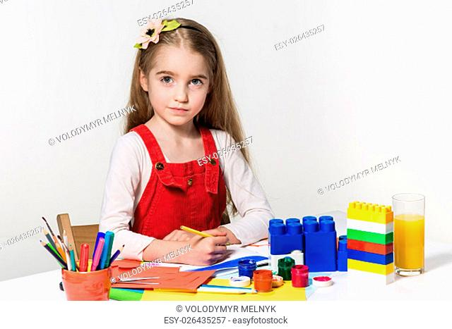 The cute little girl drawing with paint and paintbrush at home
