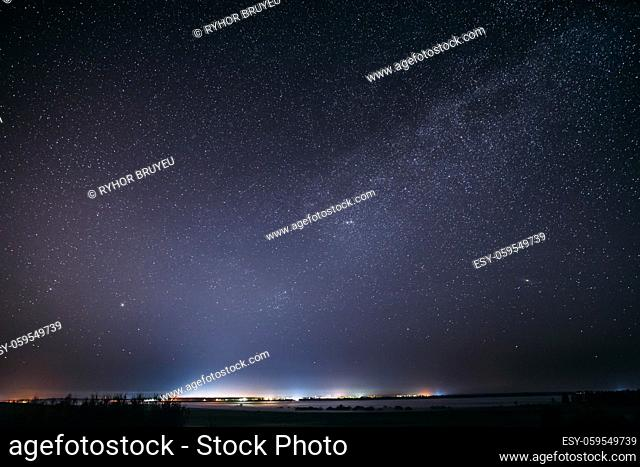 Night Starry Sky With Glowing Stars Above Landscape With City Lights. Dark Night Starry Sky Above Ground