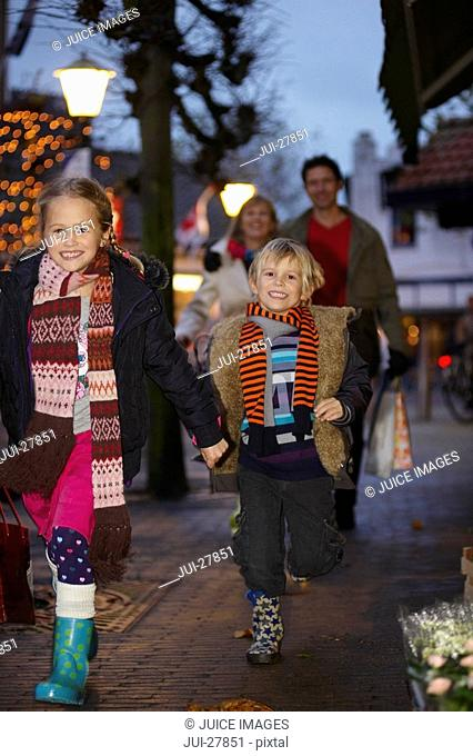Two children walking down a street with their parents following behind