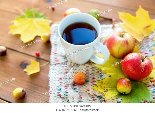 season, drink and morning concept - close up of tea cup on wooden table with autumn leaves and scarf