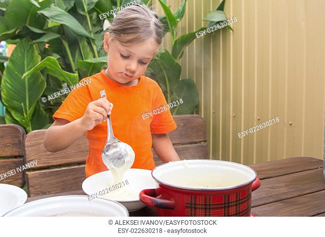 Four-year girl on breakfast imposes a ladle into a bowl semolina